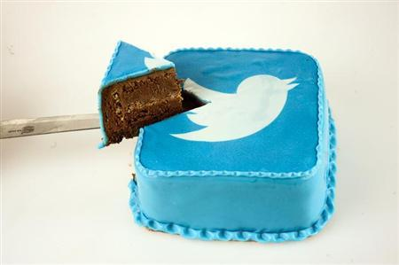 A person takes a slice of cake which is decorated in blue icing sugar with a Twitter logo at a bakery in Skopje, in this picture illustration taken September 10, 2013.
